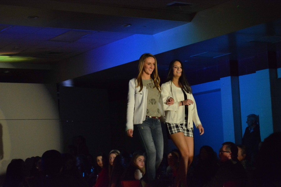 Molly Kauffman and Sophia Das link arms to walk down the runway.
